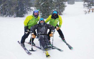 Kyle Zych poses with BOEC adaptive ski instructors