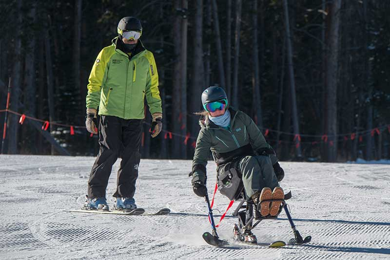 Frank on an adaptive ski lesson with a mono skier