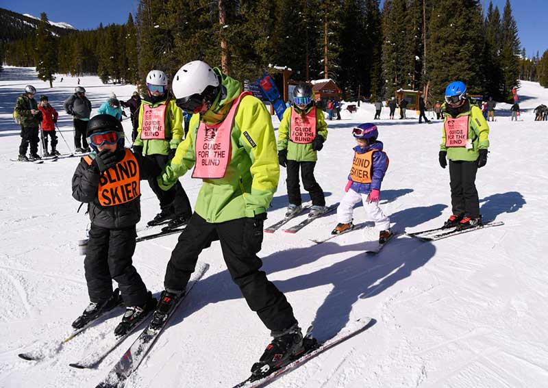 Frank's twin stepdaughters, Grace & Lily (background), volunteer on an adaptive ski lesson.